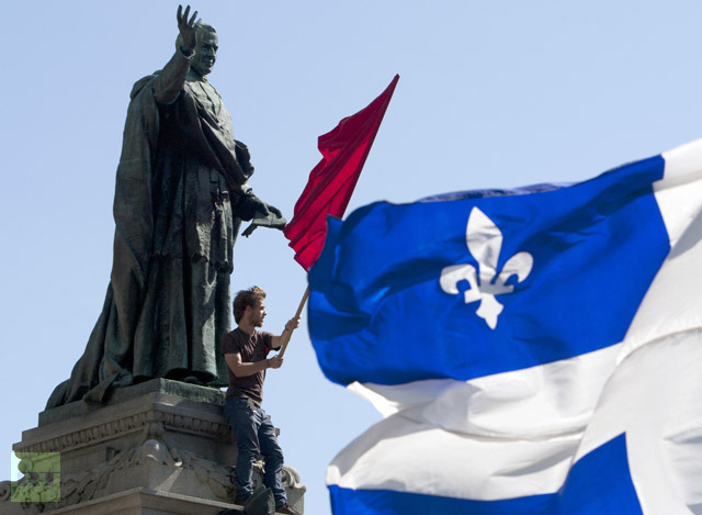 A protester waves a flag during a march against student tuition fee hikes in downtown Montreal