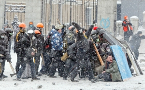 Pro-European protesters take cover behind improvised shields during clashes with riot police in Kiev January 22, 2014.